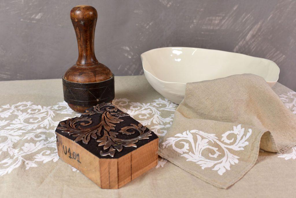 Hemp napkin, ceramic bowl, and pear wood block and hammer atop a block-printed, organic hemp tablecloth