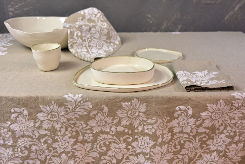 Natural hemp tablecloth - the table is set with linen napkins and ceramic tableware