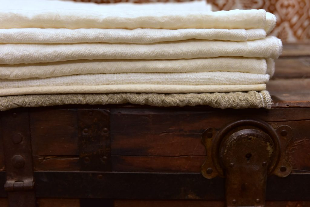 Linen fabrics folded and placed atop a mahogany cabinet