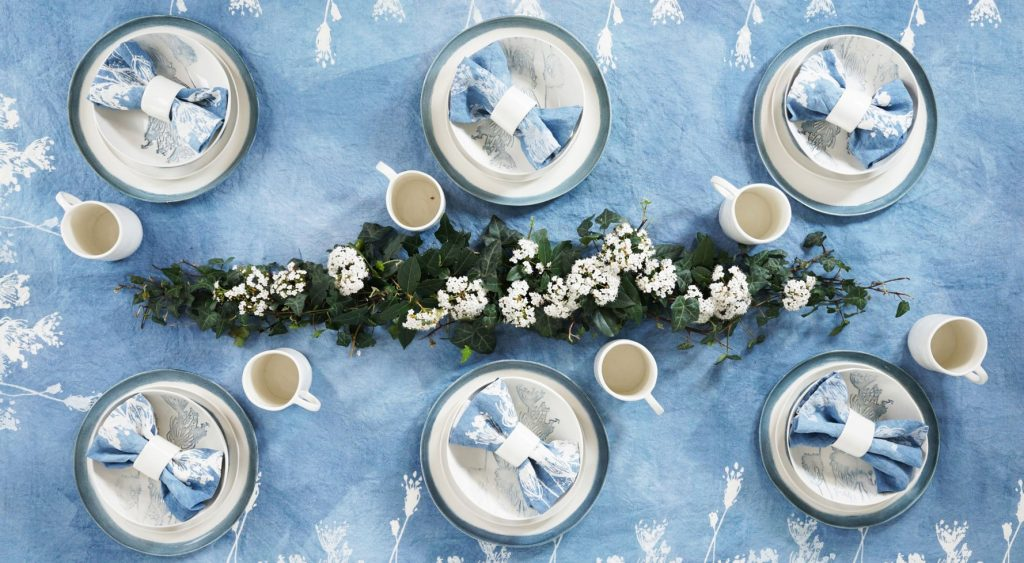 Bertozzi blue linen tablecloth, the table is set with ceramic tableware, linen napkins, mugs, and an elaborate floral table display