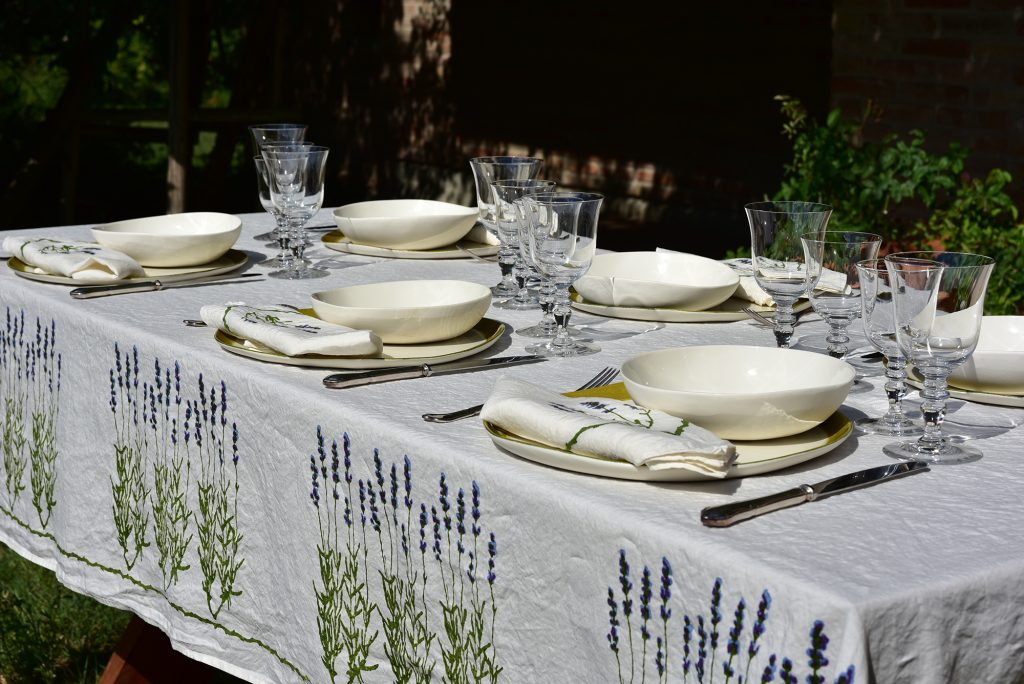 Hand-printed linen tablecloth, featuring a lavender design. Table is set outside, with beautiful glassware and ceramic bowls.