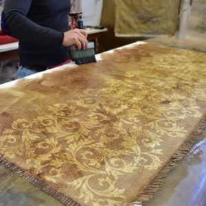 Linen Throw - Hand-painted and Hand-printed - Acanthus Leaves/Lime Green - Photo shows the process of creation, the craftsmen are using a method known as 'negative printing', 'negative printing', during which designs are painted onto the organic linen using wax