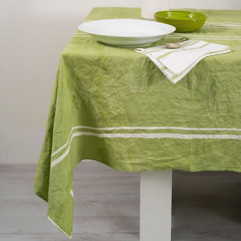 Linea green hand-crafted linen tablecloth. Upon the linen tablecloth, a ceramic plate, bowl and linen napkin are placed