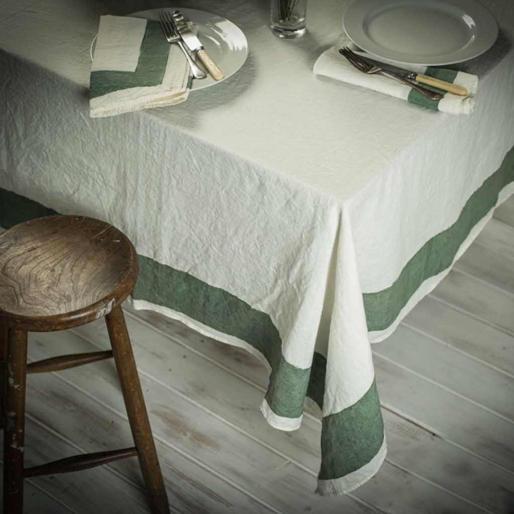 Hand-painted italian linen tablecloth featuring a cornice sage design. Matching napkins are placed atop dinner plates
