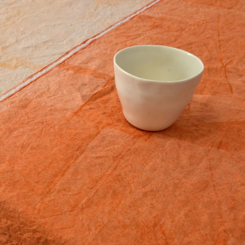 Clic orange hand-painted linen tablecloth. Upon the linen tablecloth, a ceramic mug is placed