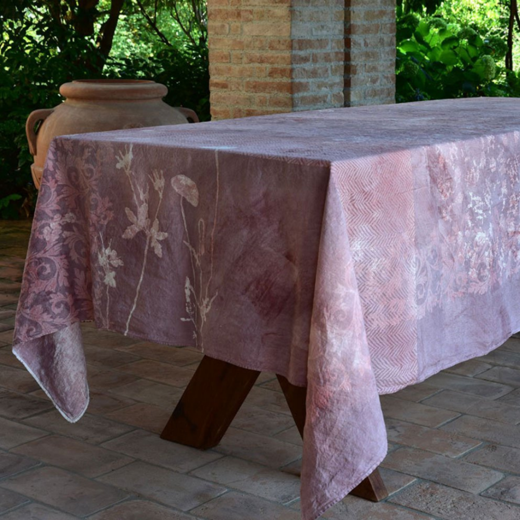 Malva hand-painted linen tablecloth placed atop a table outside in front of a brickpillar