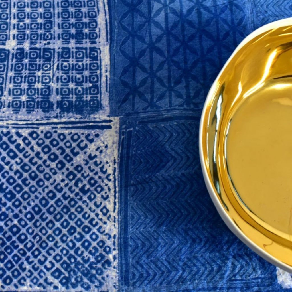 Taormina blue hand-painted linen tablecloth. Upon the linen tablecloth, a copper bowl is placed