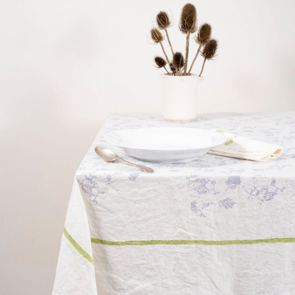 Hand-printed linen tablecloth, foglia green colour with a white background and flower table display