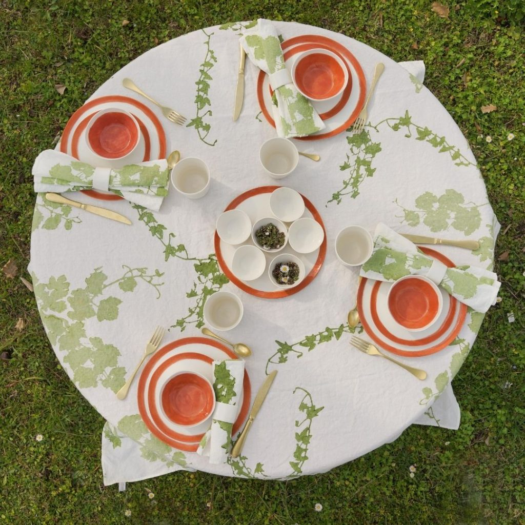 Hand-printed round linen tablecloth featuring a green floral pattern, placed on a table outside