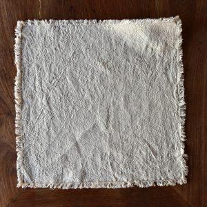 hemp napkin (dark cream) - hemp linen napkin with fringes - image displays napkin laid out on wooden floor