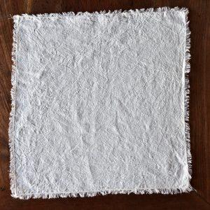 hemp napkin (light cream) - hemp linen napkin with fringes - image displays napkin laid out on wooden floor